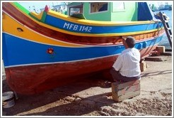 Man varnishing his boat next to Marsaxlokk Bay.