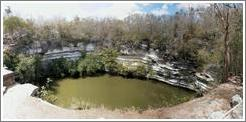 "A panoramic shot of the ""sacred well,"" or ""well of the sacrifices."" This is a natural well, or ""cenote.""   Chichen Itza."