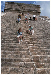 People sliding down on their butts from the pyramid.  Chichen Itza.