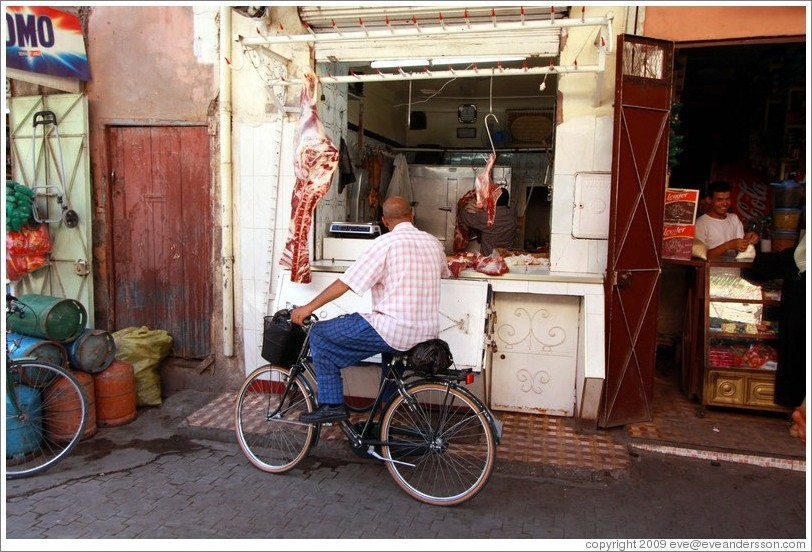 Man on a bicycle in front of a butcher in the Medina.
