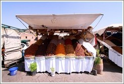 Boy asleep, manning a dried fruit stand in the midday heat, Jemaa el Fna.