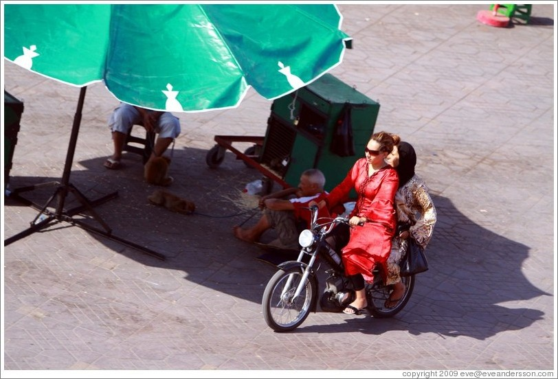 Women on a scooter, riding near man with monkeys, Jemaa el Fna.