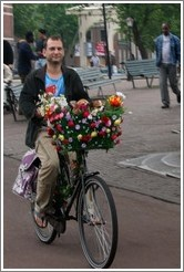 Man on bicycle with flowers and dogs.