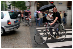 Bicyclist holding umbrella.  Dam Square, Centrum district.