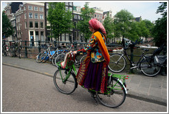 Colorfully dressed woman riding bicycle.  Bridge over Singel canal, Centrum district.