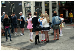 Women dressed in schoolgirl clothes, corner of Prins Hendrikkade and Nieuwendijk, Centrum district.