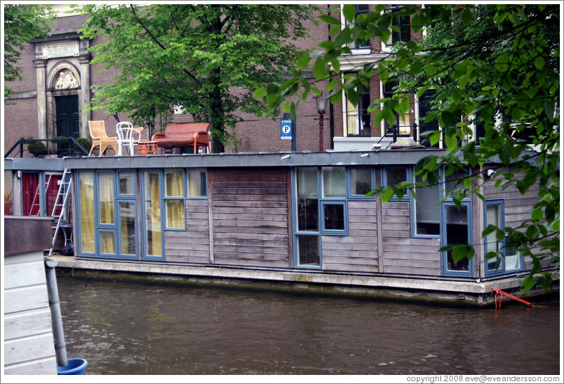 Houseboat with furniture on top, Prinsengracht canal, Jordaan district.