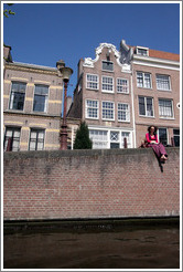Barefoot woman enjoying the sun by a canal.  Leidsegracht, Jordaan district.