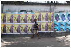 Man walking in front of posters that say Eti Keta and Reelect Fasholm.