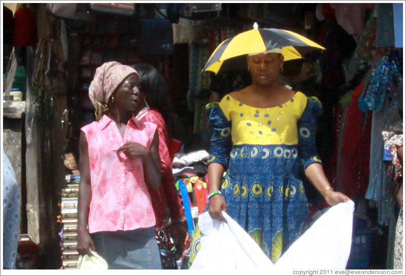 Two women talking. One wears an umbrella hat.
