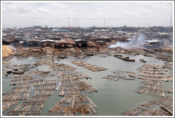 Timber being dried with fire. Makoko, a slum on the Lagos Lagoon.