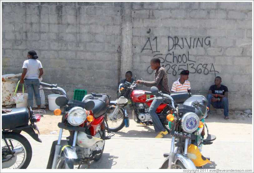 Kids and motorcycles in front of A1 Driving School written on a wall. Victoria Island.
