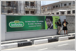 Man and woman speaking in front of a billboard, Maroko Road, Victoria Island.