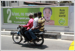 Three men on a motorcycle passing a glo billboard. Maroko Road, Victoria Island.