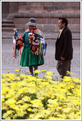 Female vendor in traditional wear and man in modern wear. Plaza de Armas.
