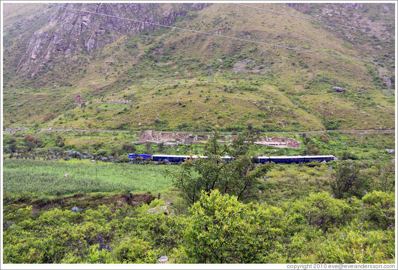 Inca ruins with a train passing by, seen from the Inca Trail.