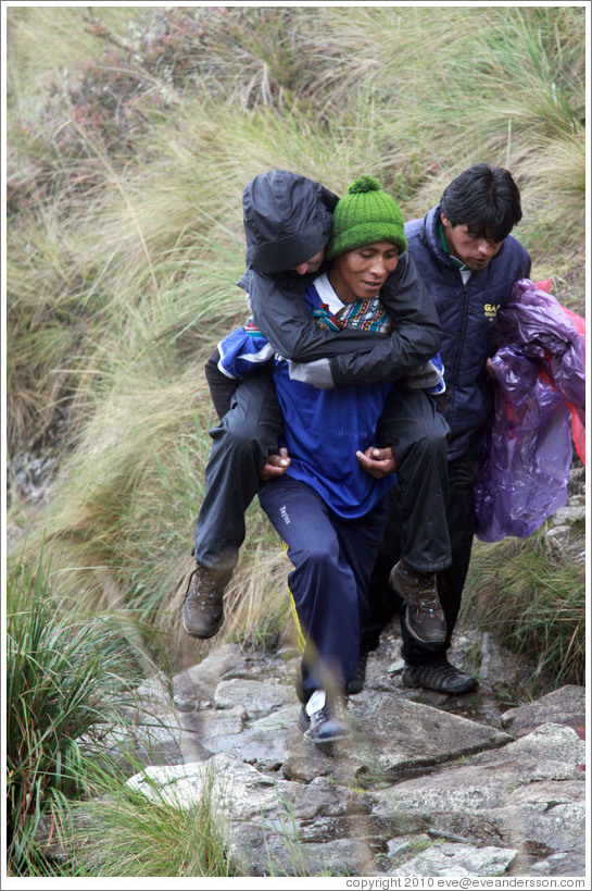 Sick woman carried by a porter on the Inca Trail.