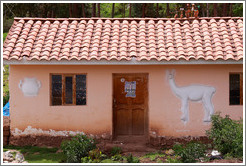 House near the Puca Pucara ruins, with a relief of a jar and an alpaca.