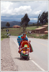 Woman walking with a baby in a stroller along the road near the Puca Pucara ruins.