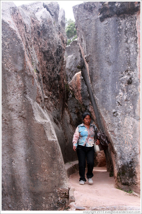 Woman walking between tall rocks, Qenko ruins.
