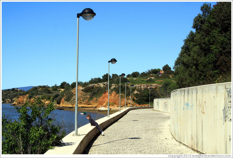 Child looking out to the sea, coastal path, Alvor.