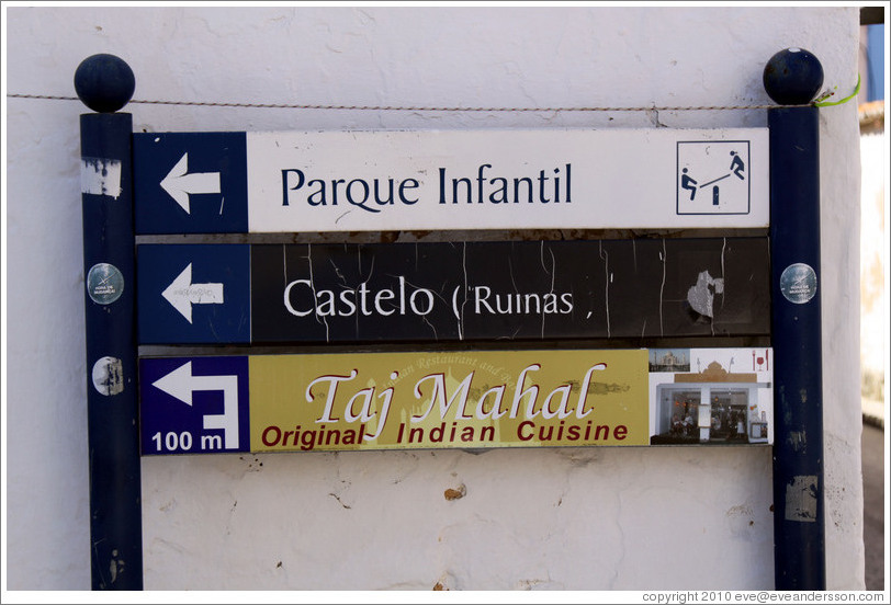 Sign reading Parque Infantil (playground), Castelo Ruinas (castle ruins), and Taj Mahal Original Indian Cuisine.