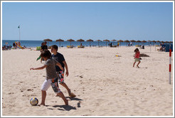 Kids playing soccer on the beach.