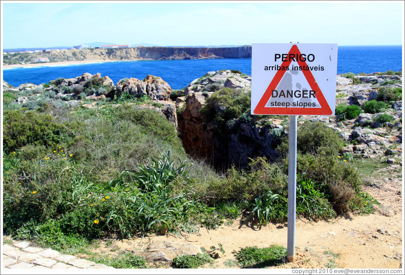 "Sign reading ""Perigo arribas inst?is"", which loosely translates as ""Come this way for a great photo op.""  Fortaleza de Sagres (Sagres Fortress)."