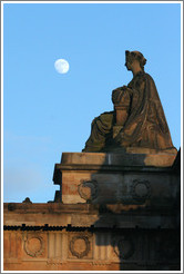 The moon appearing to hover near a statue of a woman atop the Royal Scottish Academy‎ building.