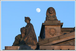 The moon appearing to hover near statues of a woman and a sphinx atop the Royal Scottish Academy‎ building.