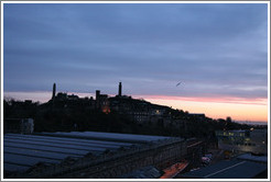 Edinburgh Waverley railway station's roof, with Calton Hill in the background, at sunrise.