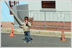 Boy drinking a can of Coke. Chiappini Street, Bo-Kaap.