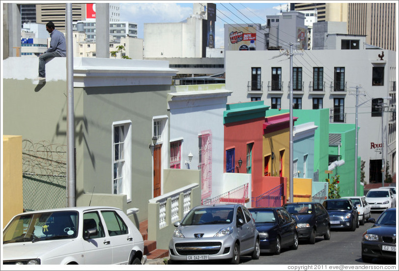 Hout street, Bo-Kaap.  A man is sitting on the roof at the left.