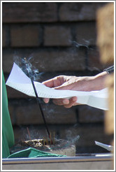 Hand holding a paper behind burning incense. Tana Baru cemetery, Bo-Kaap.