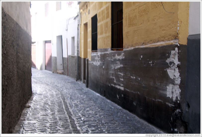 A very narrow portion of Calle de San Juan de los Reyes, Albaic? The wall has been scraped up by cars that pass too close.