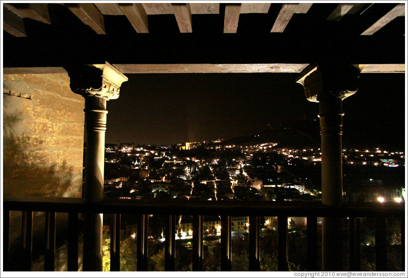 Balcony in Nasrid Palace, Alhambra overlooking Granada at night.