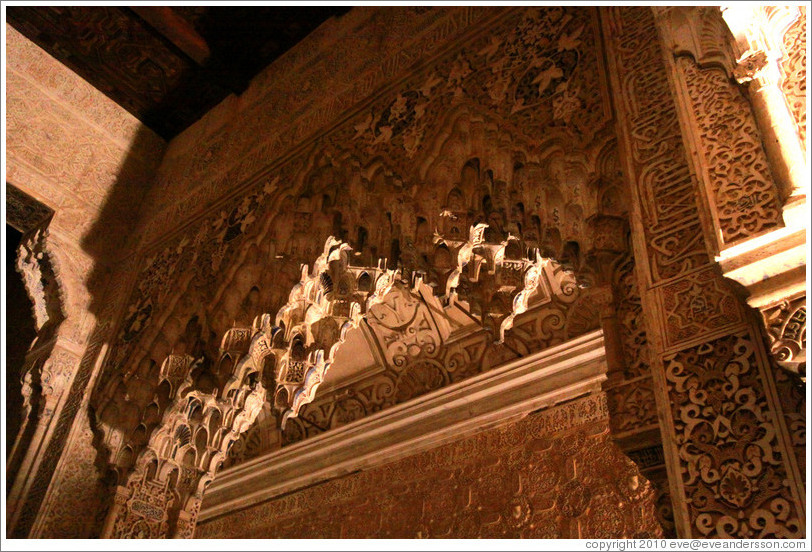 Arch adorned with muqarnas, Patio de los Leones, Nasrid Palace, Alhambra at night.
