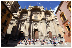 People enjoying the sun on steps in from of the Granada Cathedral.