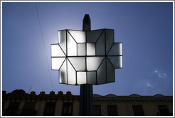 Street light during the day, with the sun above it.  Calle Gran V?de Col? City center.