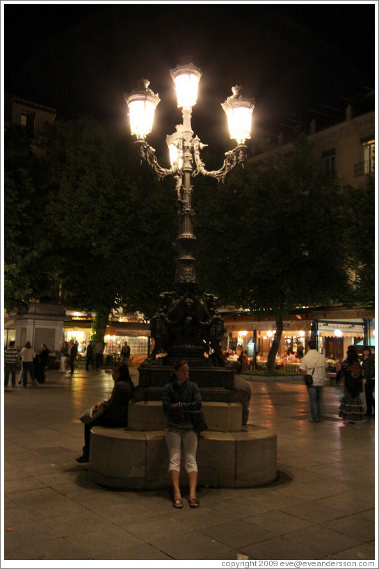 Girl sitting under lights.  Plaza de Bib-Rambla.  City center.