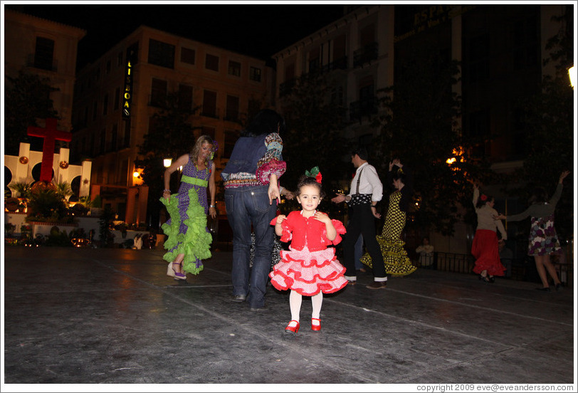 Girl in red among people dancing flamenco on the street at night during the Fiesta de las Cruces.  Plaza del Carmen.  City center.