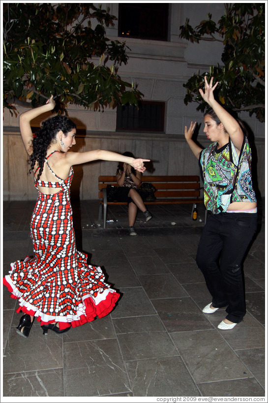 Women dancing flamenco on the street at night during the Fiesta de las Cruces.  Plaza del Carmen.  City center.