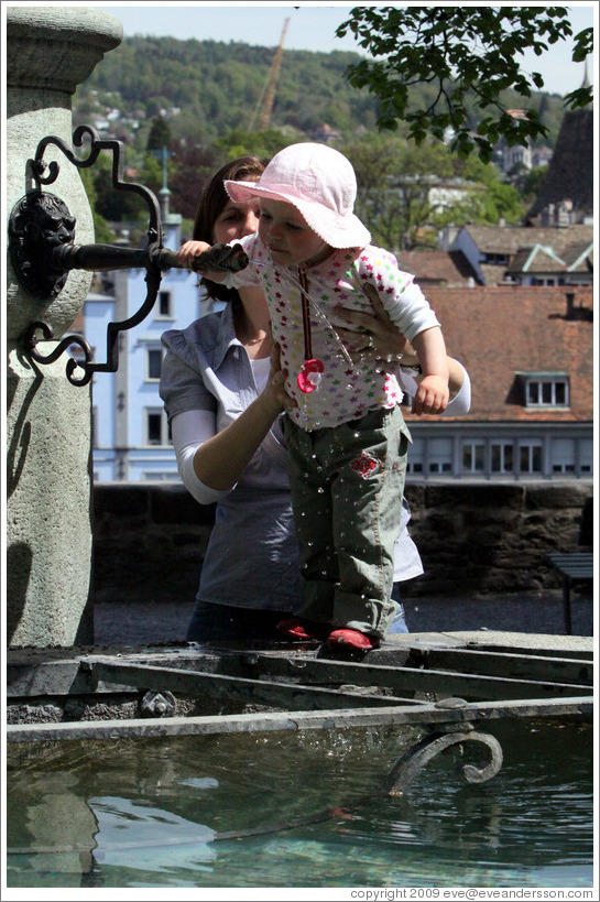 Baby drinking from fountain.  Clean, mountain water comes out of fountains in Z?rich.  Lindenhof.  Altstadt (Old Town).