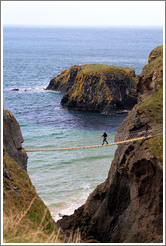 Man crossing Carrick-a-Rede Rope Bridge.
