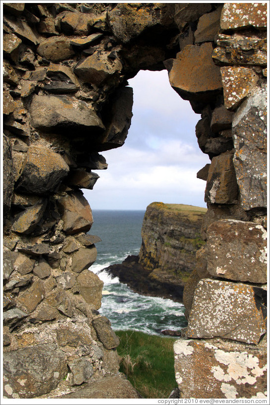 View of a sea cliff through a hole in the wall of Dunluce Castle.