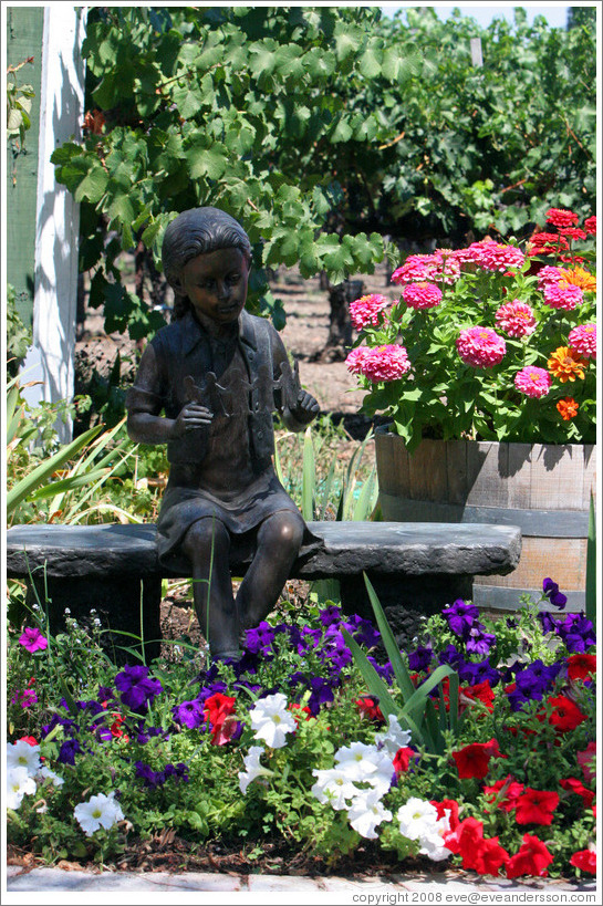 Girl sculpture surrounded by flowers.  Retzlaff Estate Winery.