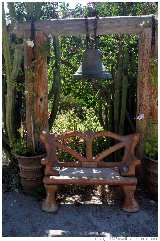 Bell and bench in garden.  San Juan Bautista Mission.