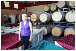 Winemaker Katy Lovell of Poetic Cellars standing among containers of fermenting grapes under blankets.