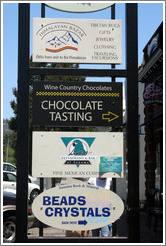 Business signs in downtown Sonoma: Chocolate Tasting, Crystals, and Himalayan products.