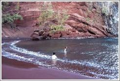 Red sand beach. Jin and Beth in water.  Hana, Maui.